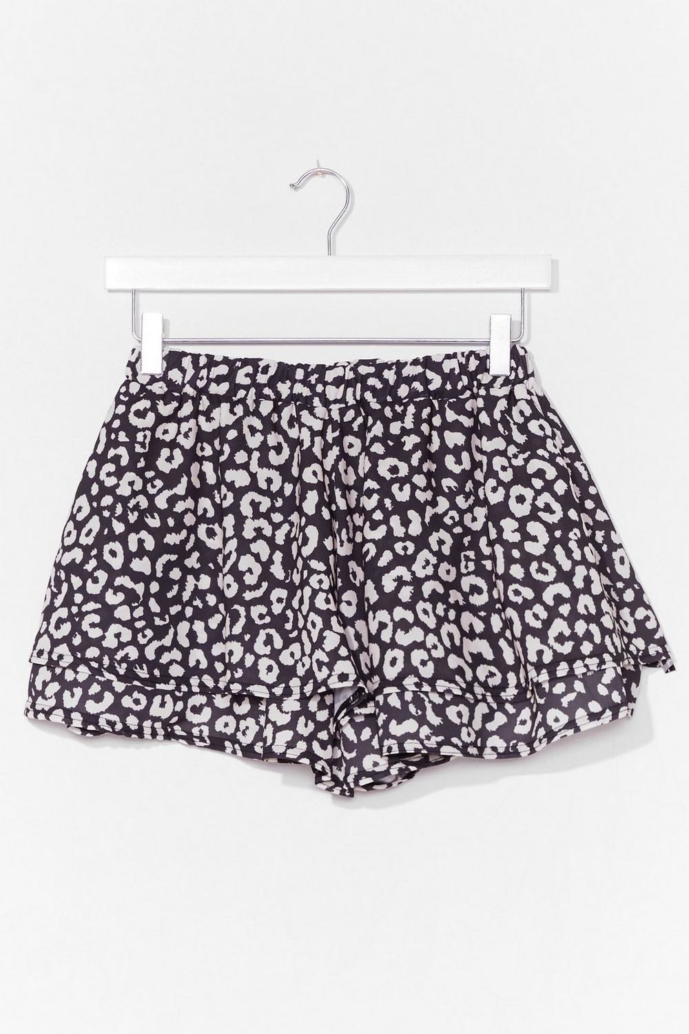 a pair of ruffled black and white leopard pattern shorts on a hanger