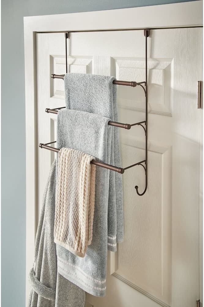 A multi-tiered shelf hanging over the bathroom door with towels and a bathroom hanging from the shelves