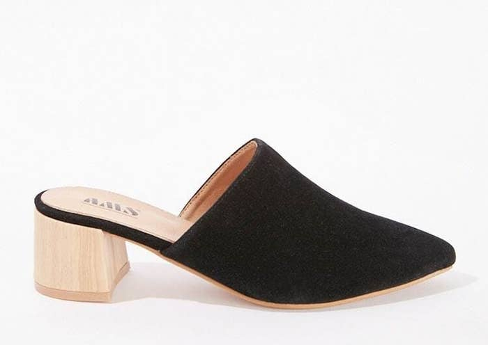 A black pointed toe mule with a faux wooden heal about two inches high