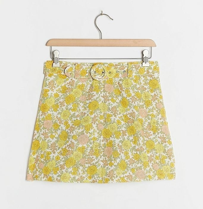 a short skort with a retro floral print of yellow and pink roses and a circular belt buckle in the same print