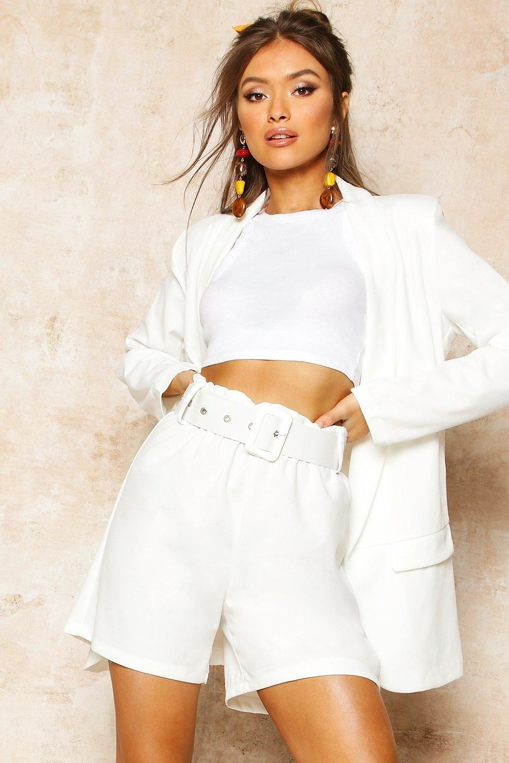 a model in the white paper bag tailored shorts with a thick white belt and rectangle buckle
