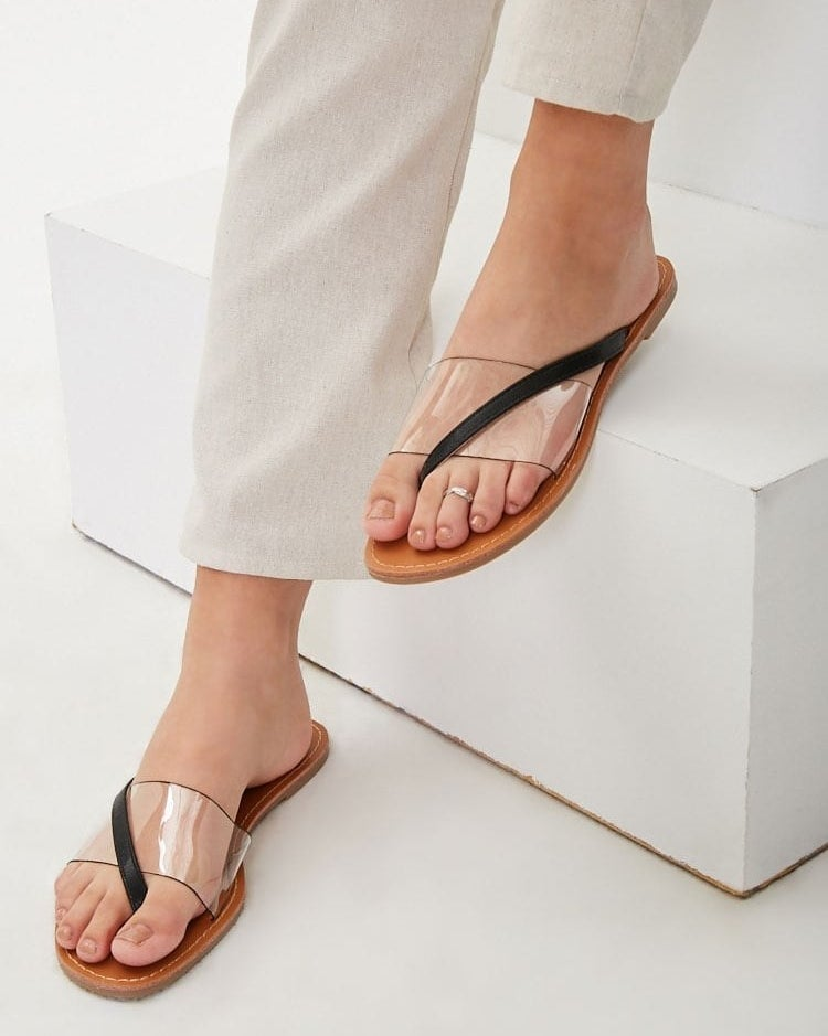 A model wearing the flat sandals, showing the clear cover above the top of their foot and a small black strap that starts at the side of the shoe and crosses over the plastic cover to fit in between the big and middle toe