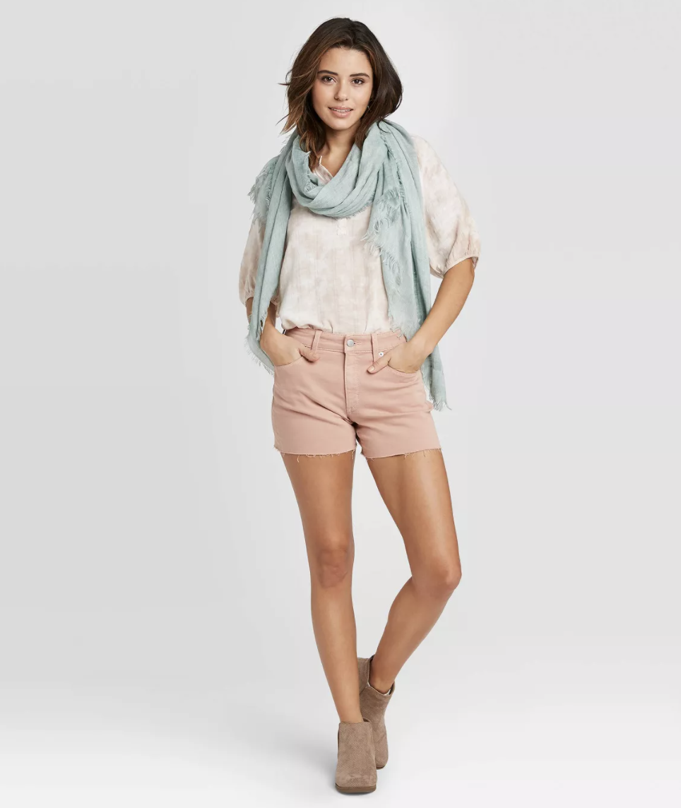 a model wearing blush pink shorts