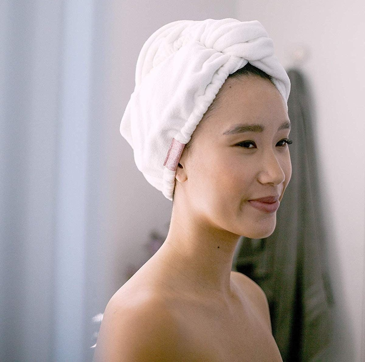 A person wearing a fluffy towel around their head