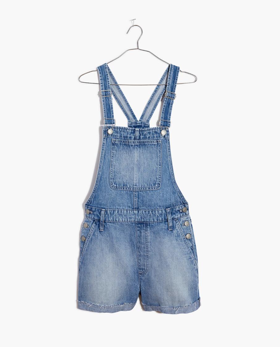 a pair of denim medium wash short overalls