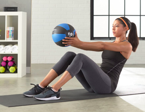Model uses blue 10-pound exercise ball to do core moves at home