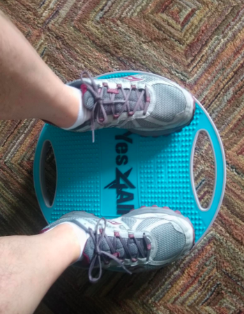 Reviewer uses blue wobble balance board to workout in their home