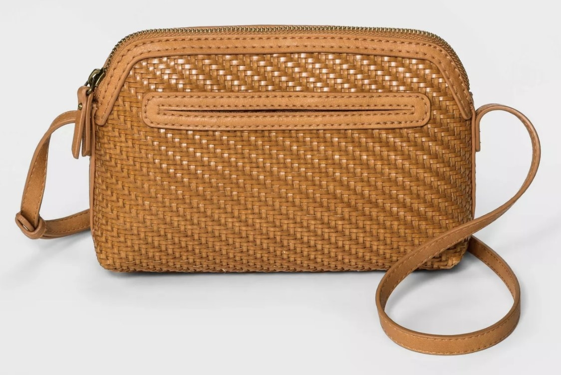 A brown woven rectangular cross body bag with a shoulder strap