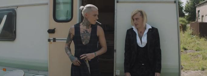 Two platinum blonde men standing in front of a caravan with the door open