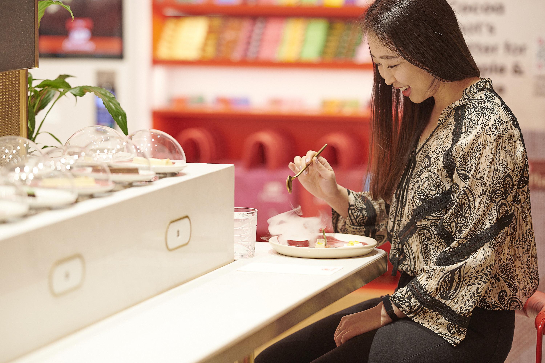 Smiling woman eating smoking dessert at table