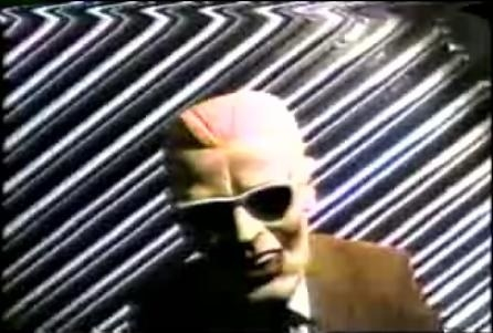 A man dressed as Max Headroom, standing in front of a distorted background