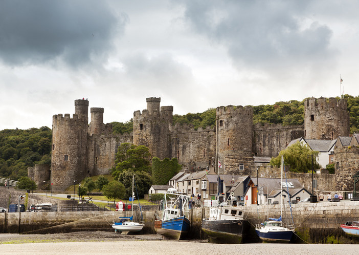 The habour with sailing boats and the castle in Conwy on a grey and cloudy day