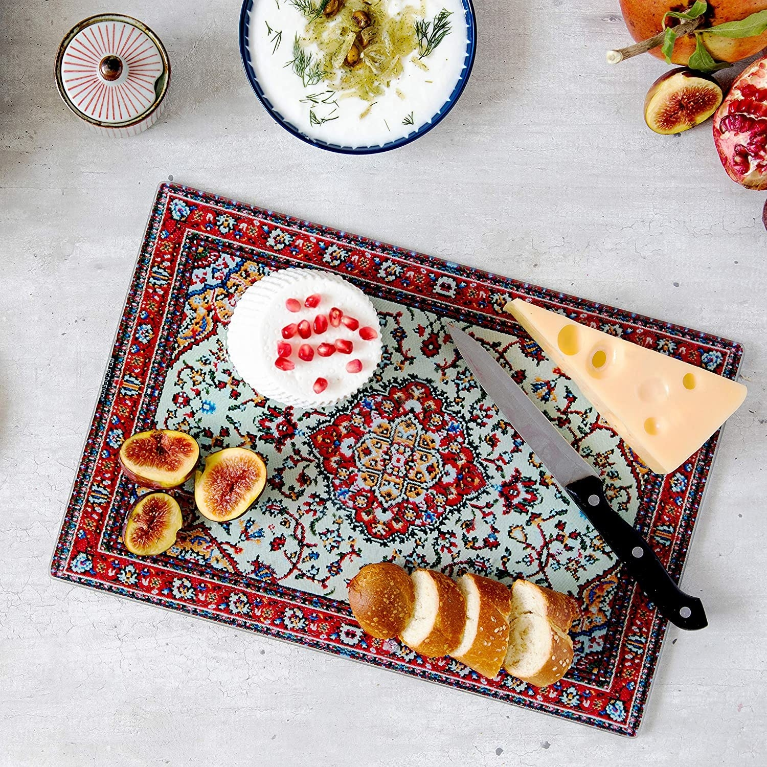 the red and blue cutting board with cheese and figs on it