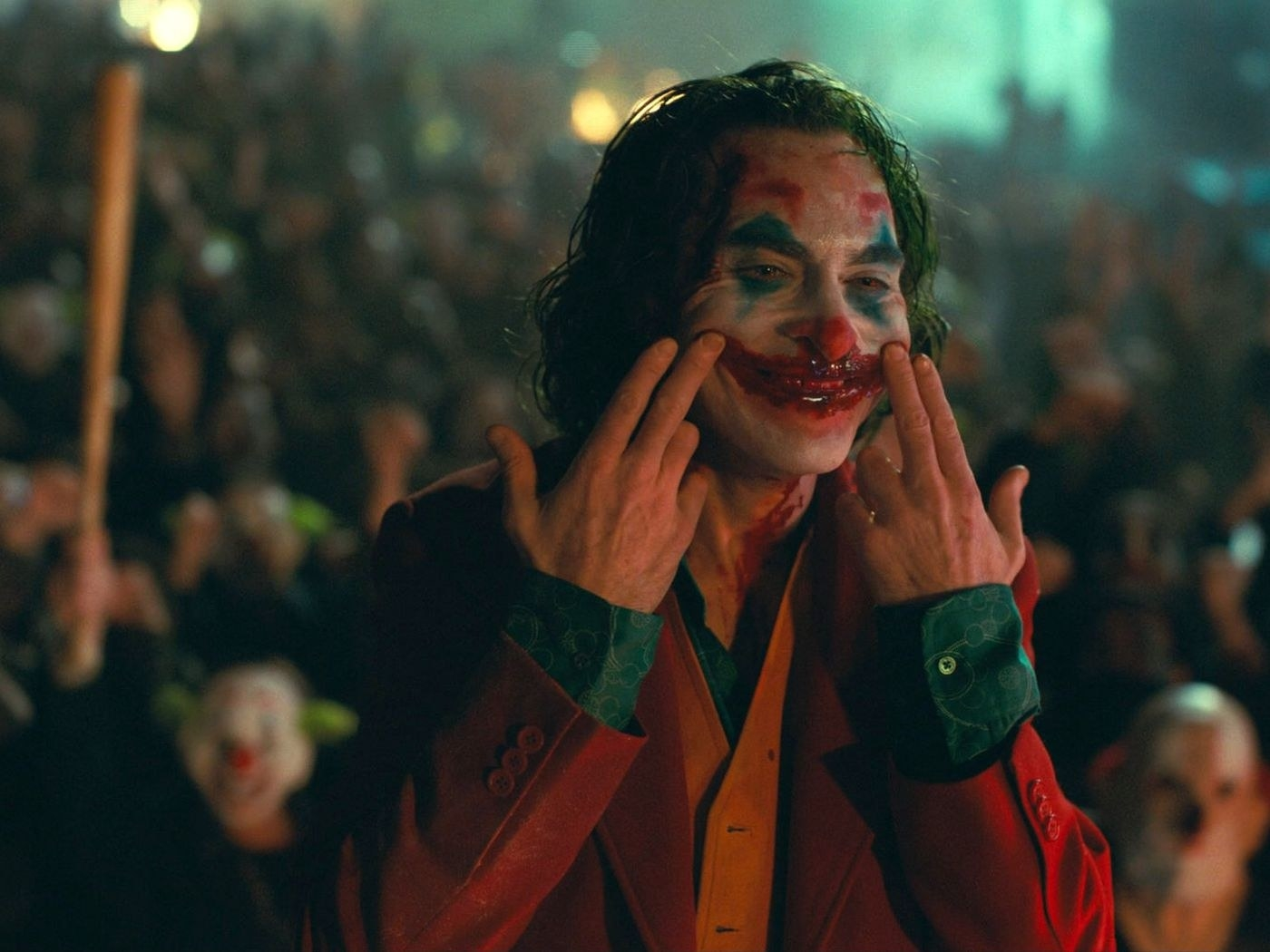 Joker raising the corners of his lips to smile while there's blood spewing down from his nose