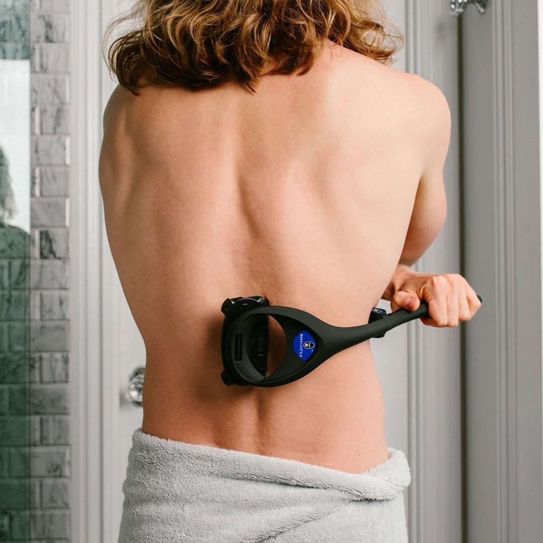 A person shaves their back with the back blade