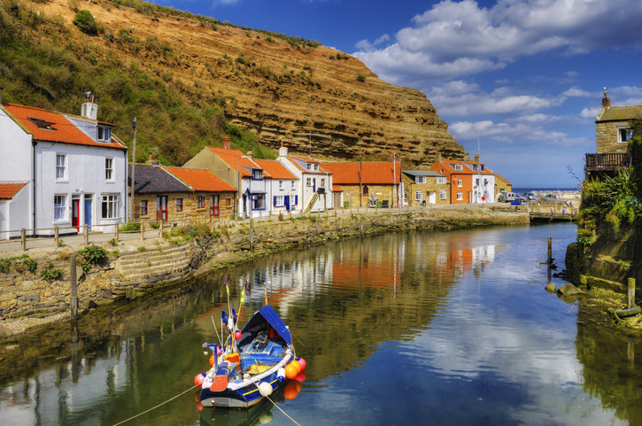 A small fishing boat is on the river in Staithes with the houses either side. You can see the beach and the sea in the distance