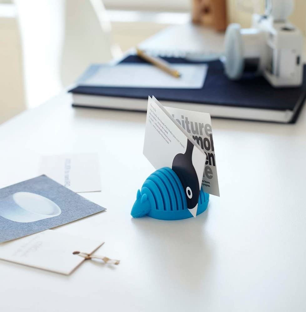 The armadillo card holder perched on a desk and holding two business cards