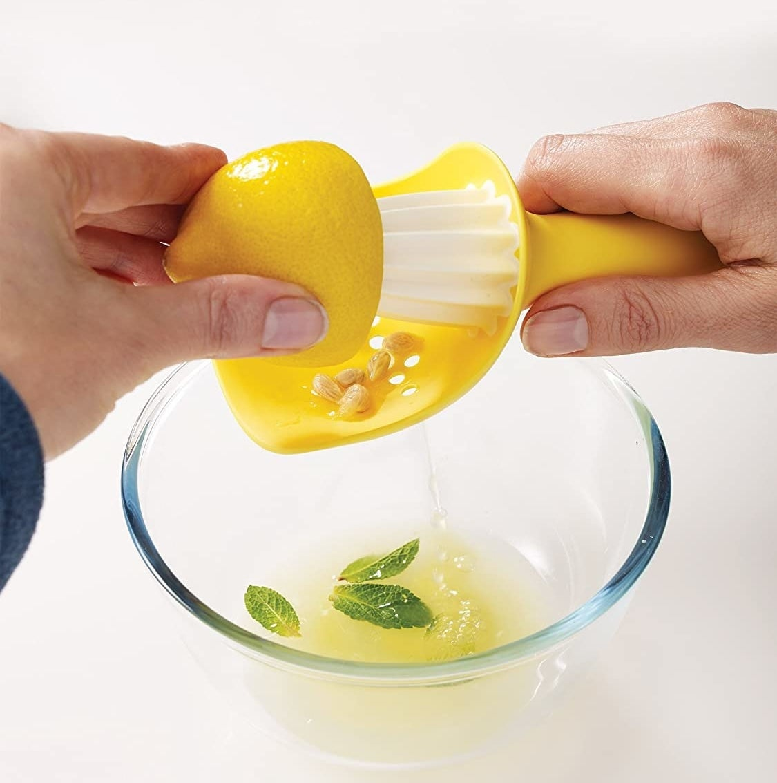 A person juices a lemon over a bowl where a few seeds are caught in the colander attachment