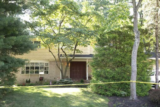 The two-story home of the judge is pictured with police tape strung between trees and bushes surrounding the property.