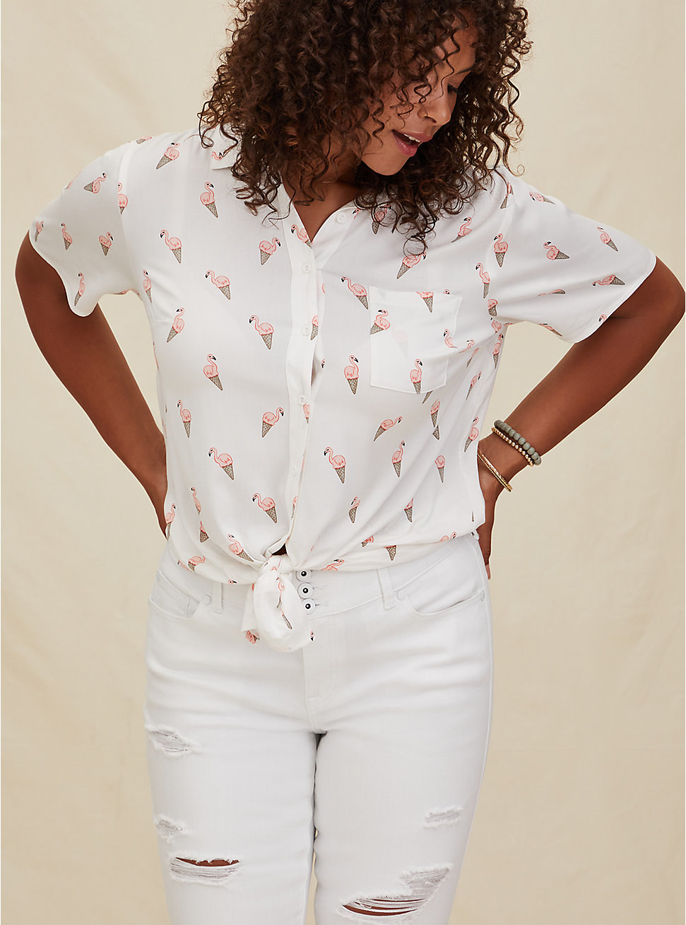 Model wearing the collared button-down shirt in white tied in the front  with a pocket on the left chest and a print of flamingos in ice cream cones all over it