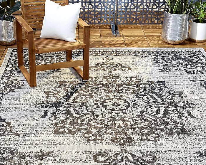 the grey and white outdoor rug with a medallion pattern on it