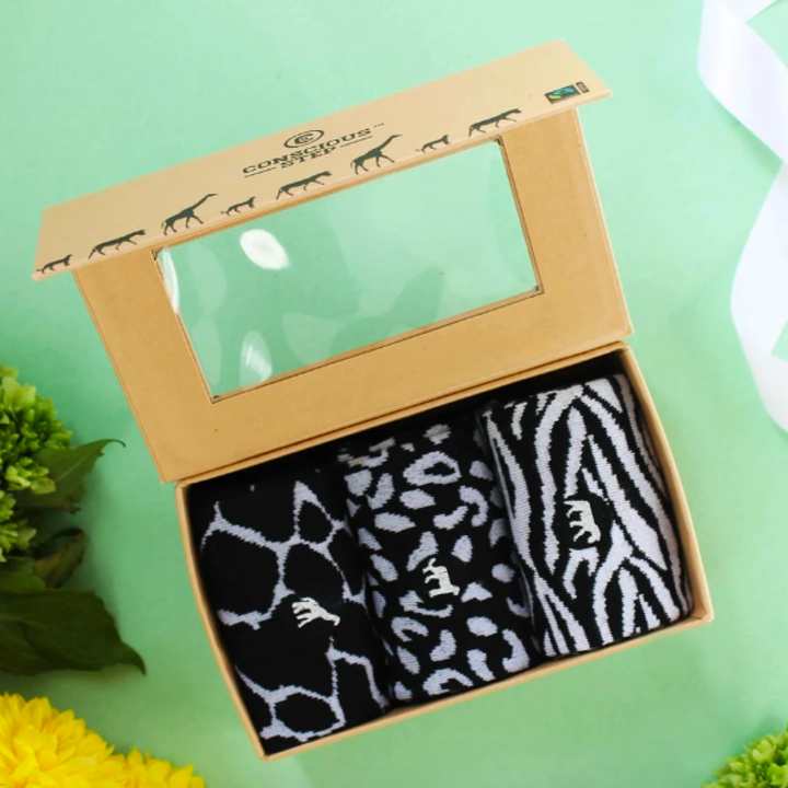 A box with three black and white socks inside, each with a different animal pattern