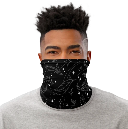 Model in a black star and feather-printed neck gaiter