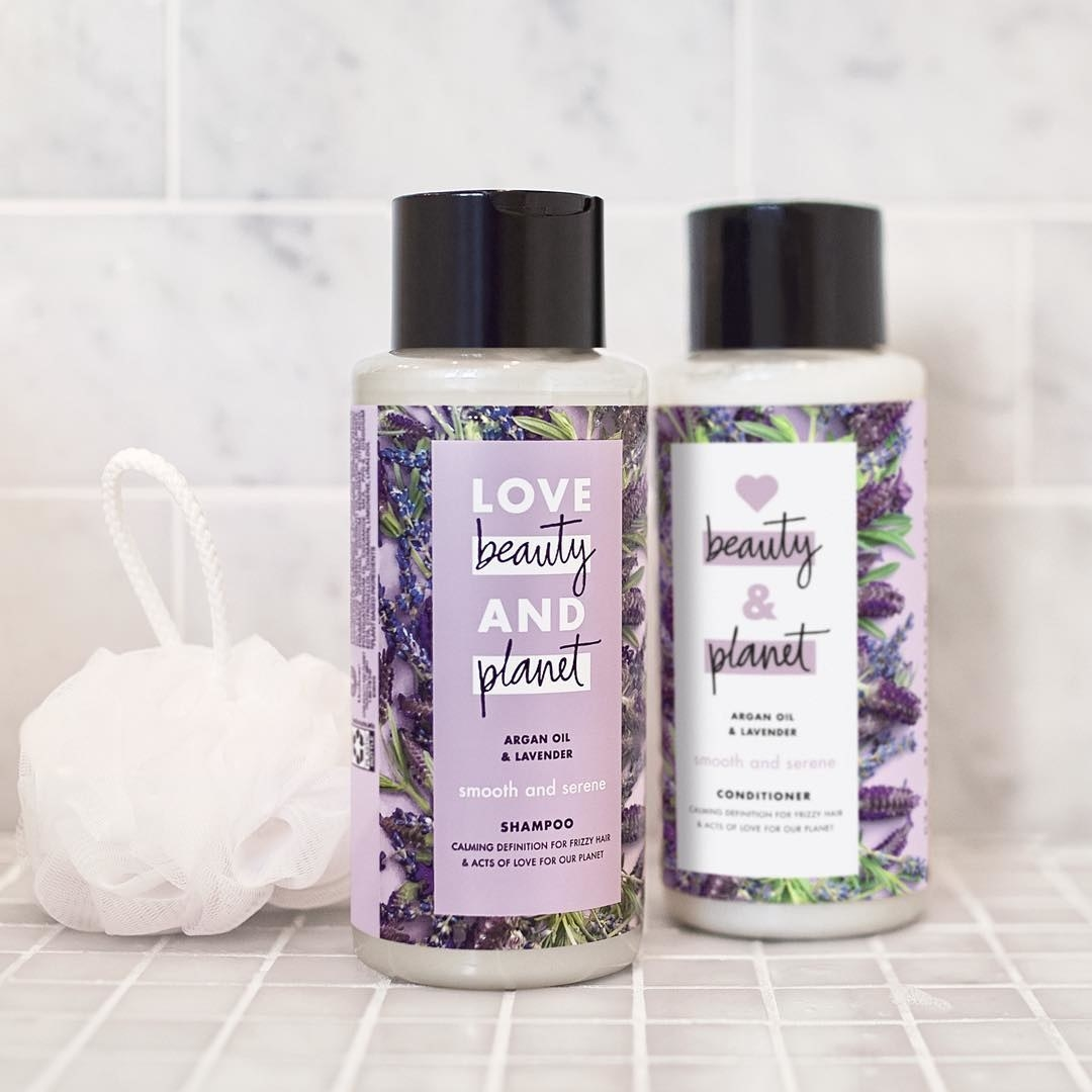 Bottles of shampoo and conditioner with a purple floral wrapper around them in a shower with a white shower pouf sitting next to them