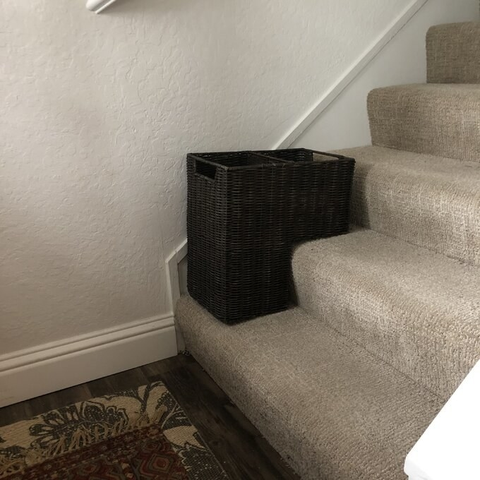The wicker basket is sitting on a carpeted staircase. It's shaped like a square with a corner cut out. That cutout corner is what sits on the steps.