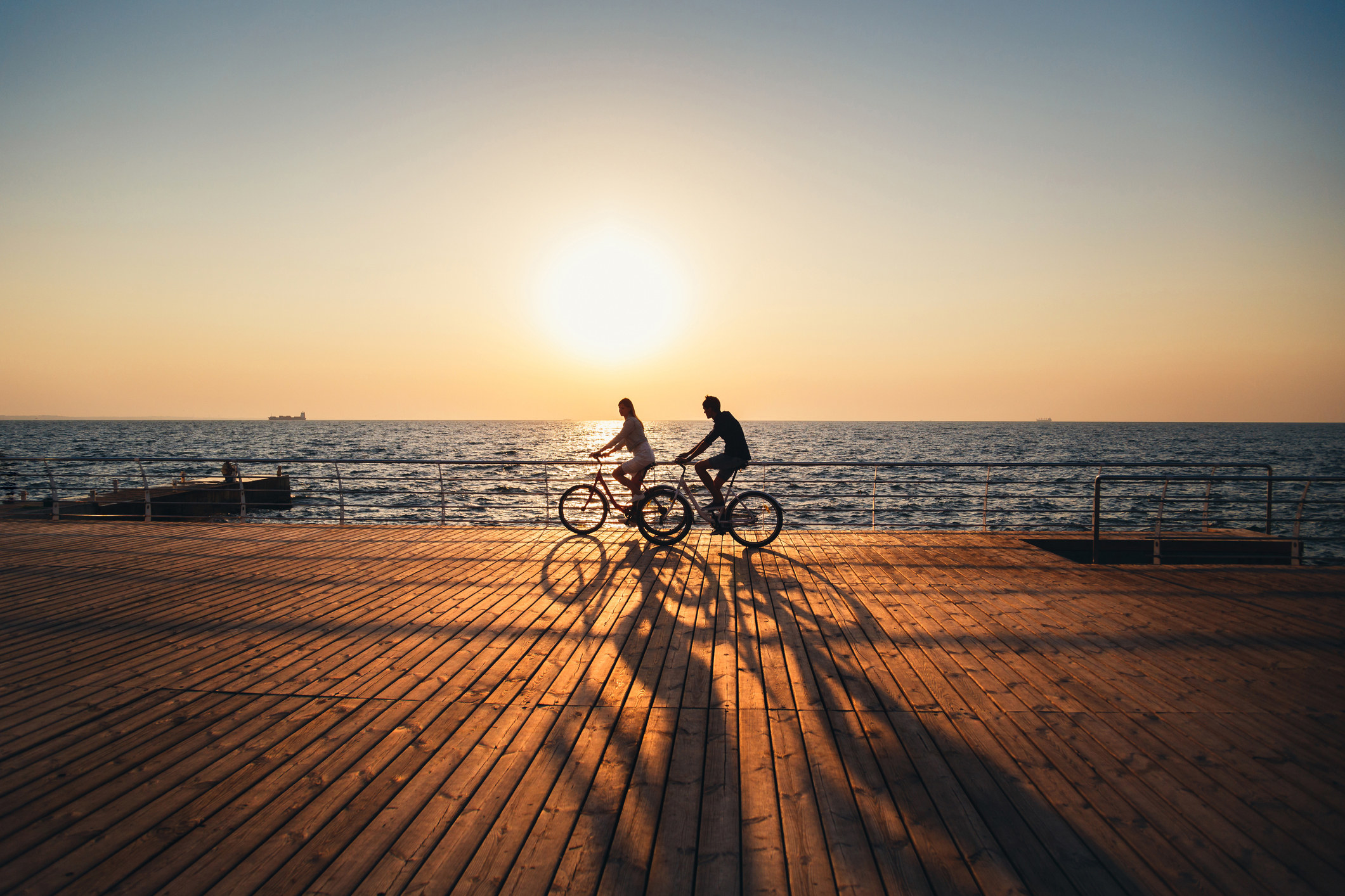 Two people riding their bikes on a boardwalk.