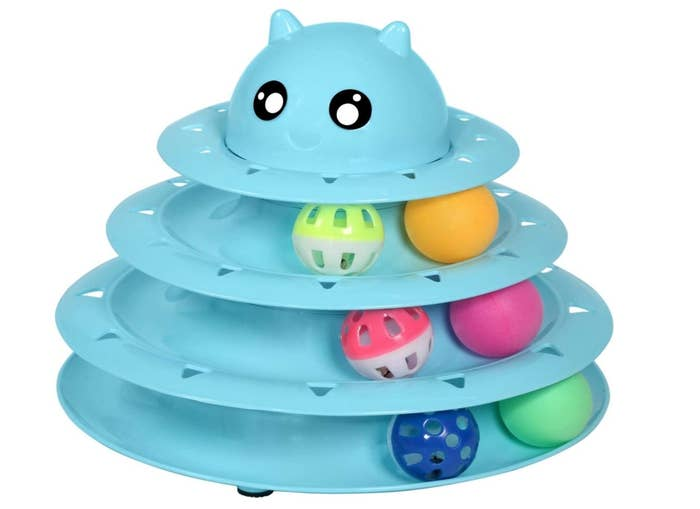 A light blue plastic cat toy with four different sized circles holding colorful balls