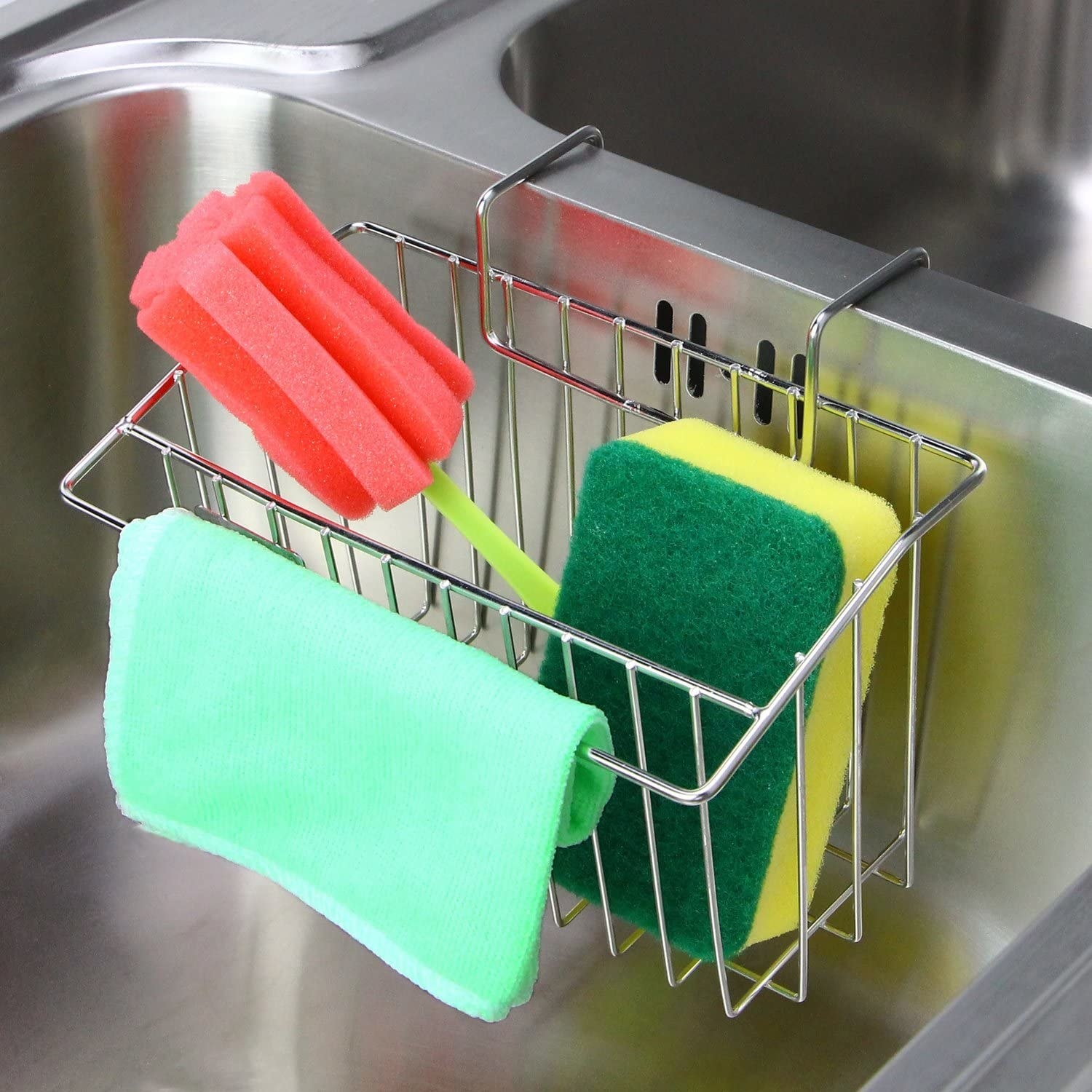 A wire mesh kitchen sink caddy hanging on the sink and holding dishwashing brushes and a sponge