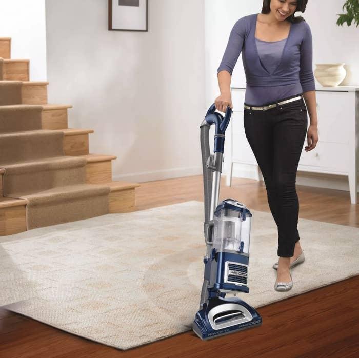 a model vacuuming the carpet