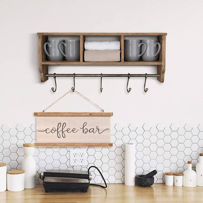 The wooden shelf hanging on the wall with mugs stored in its cubbyholes