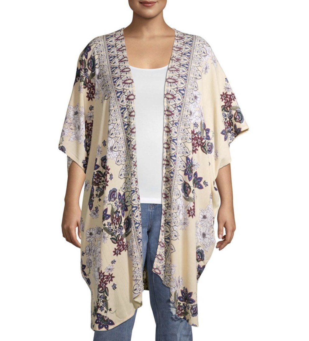 A model in an open, draped cardigan with floral designs