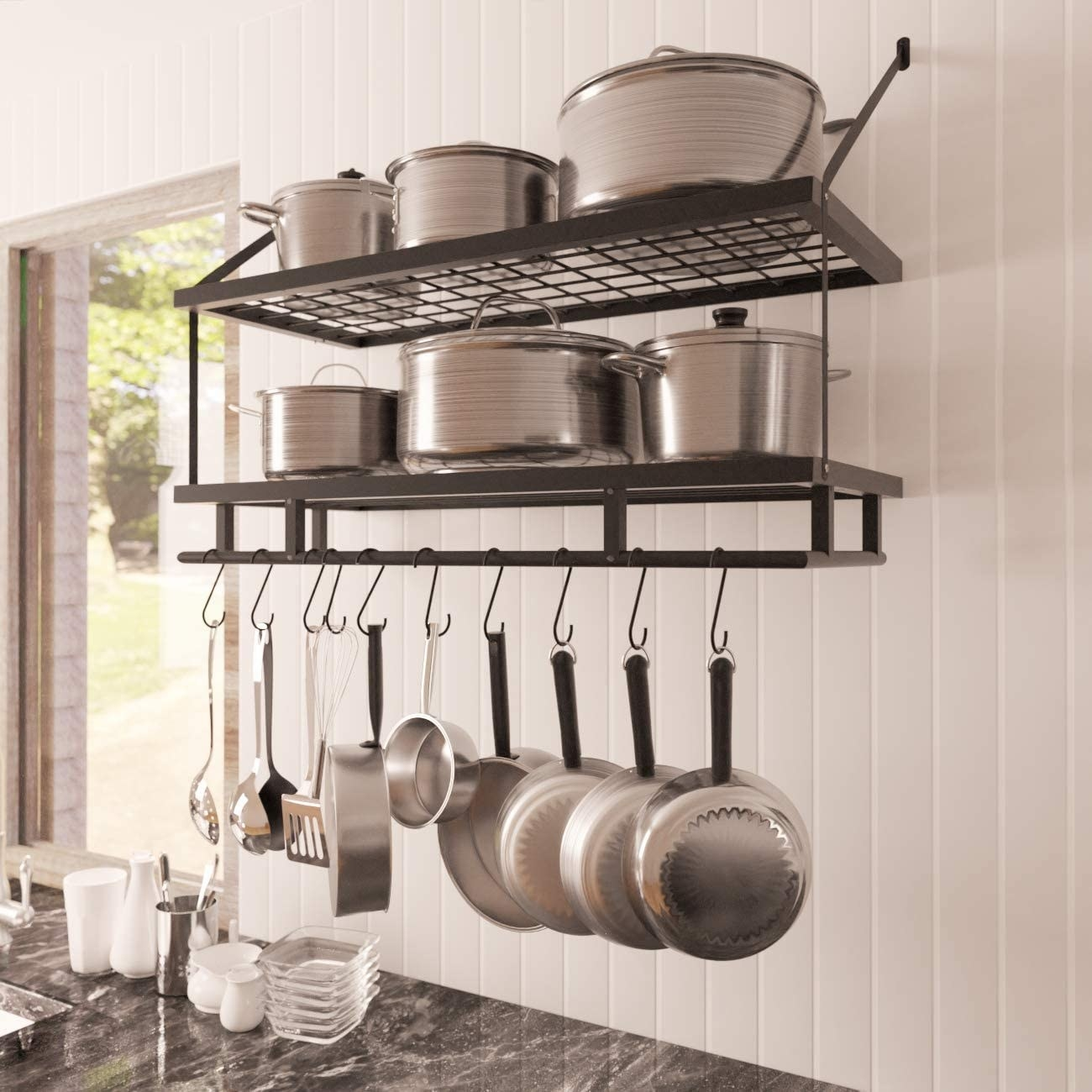 A metal shelf on a wall. with shelves for pots and hooks with pans hanging off of it