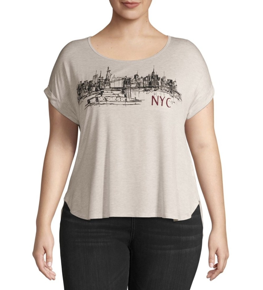 A model in a beige t-shirt with the New York city skyline
