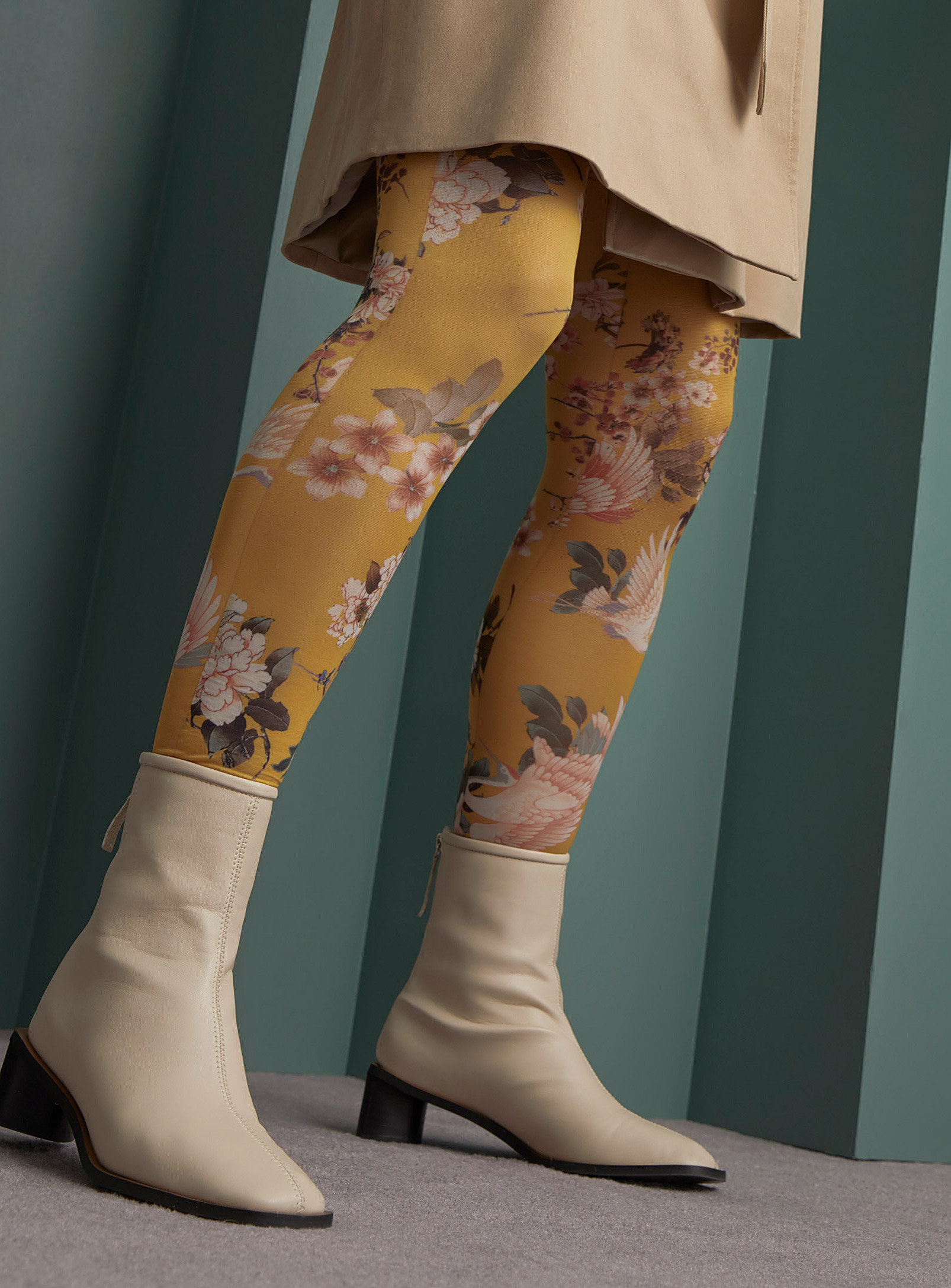 A person wearing floral tights with heeled boots