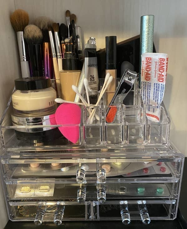 The clear makeup organizer with two full-size drawers and two half drawers and places on top to store makeup and other things