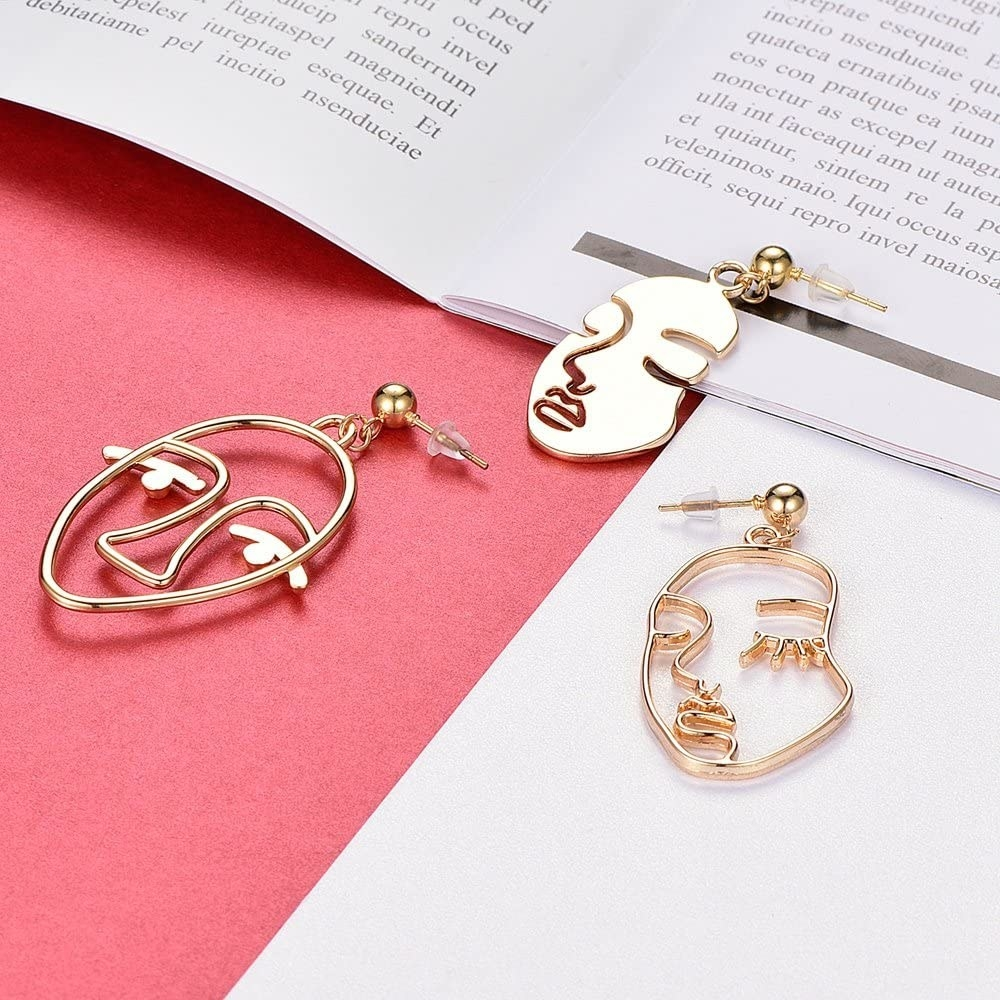 Three face-shaped metal earrings lying on a desk