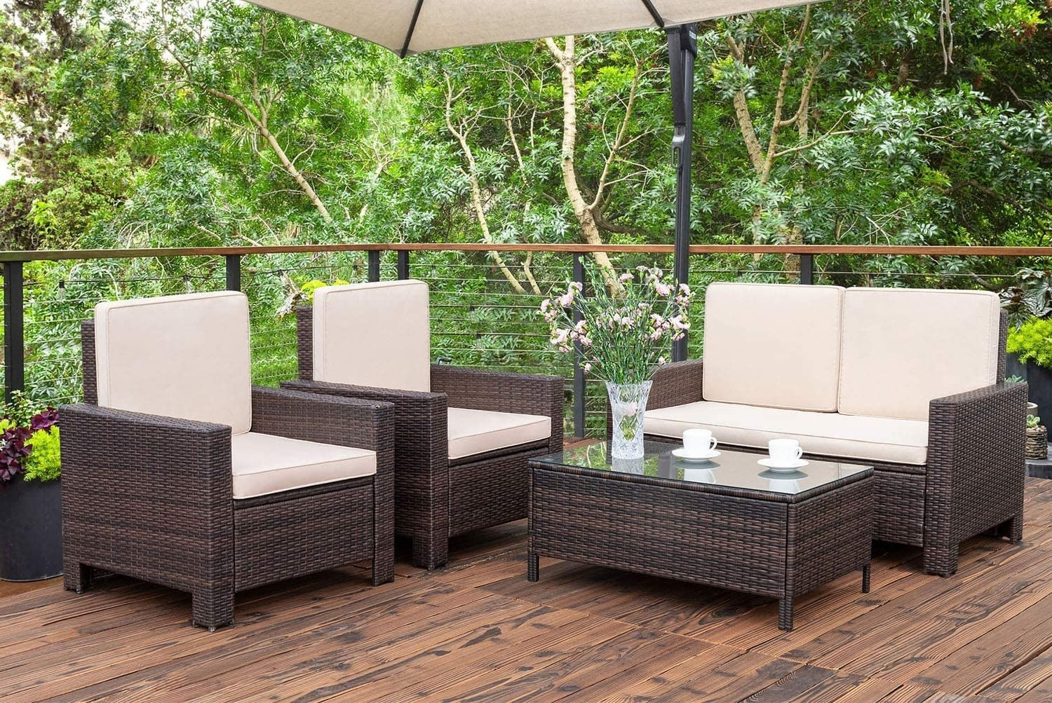two chairs, a love seat, and a coffee table with dark brown rattan bases and light tan cushions