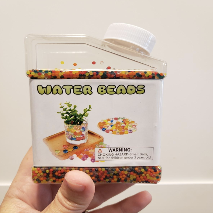 A reviewer holding up a small container of tiny tiny beads