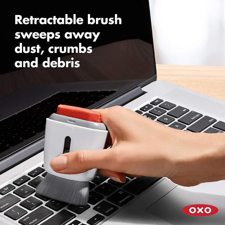 "A model's hand using the brush side of the tool to clean their keyboard, with the text ""Retractable brush sweeps away dust, crumbs and debris"""