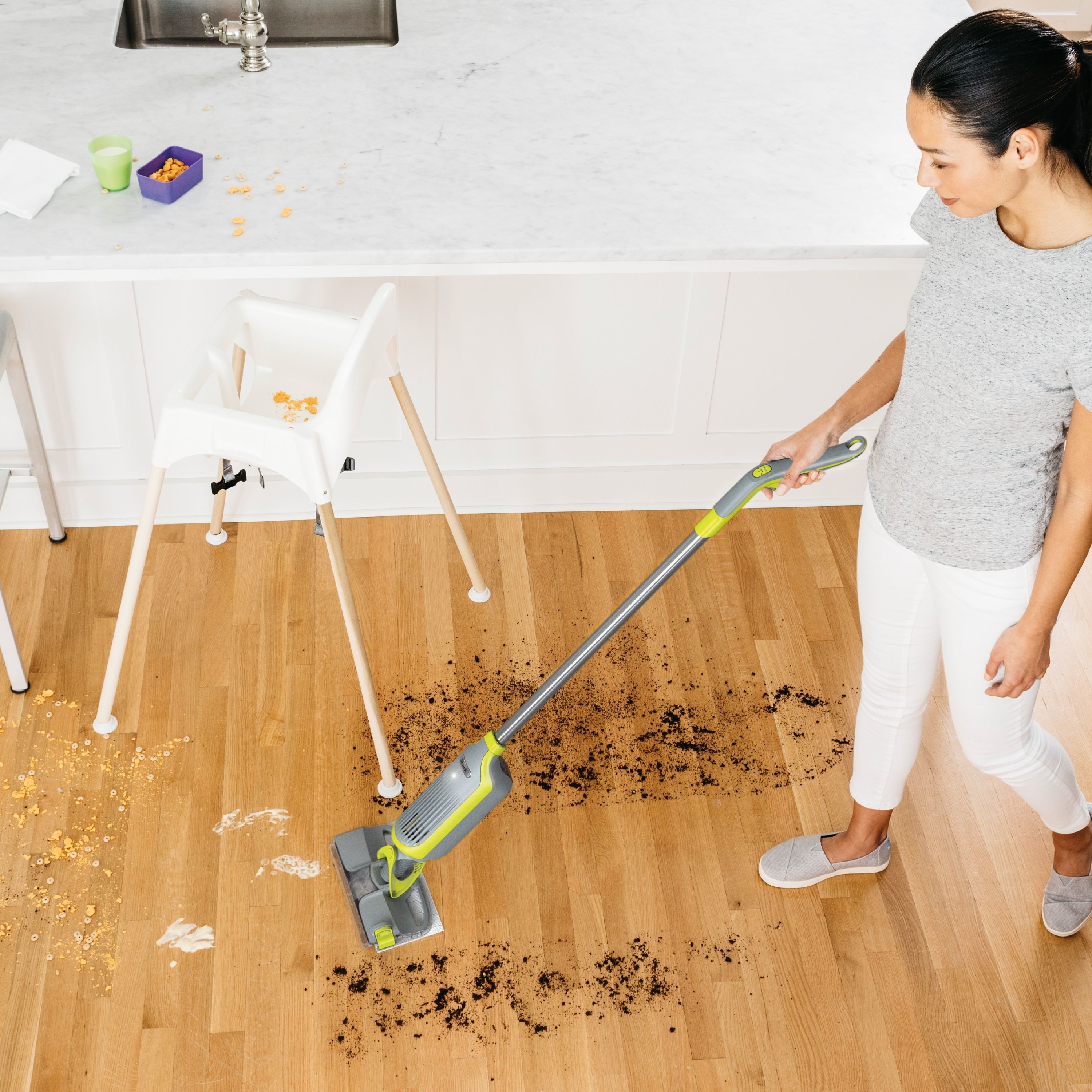 model cleaning up messy floor with the gray and lime green mop