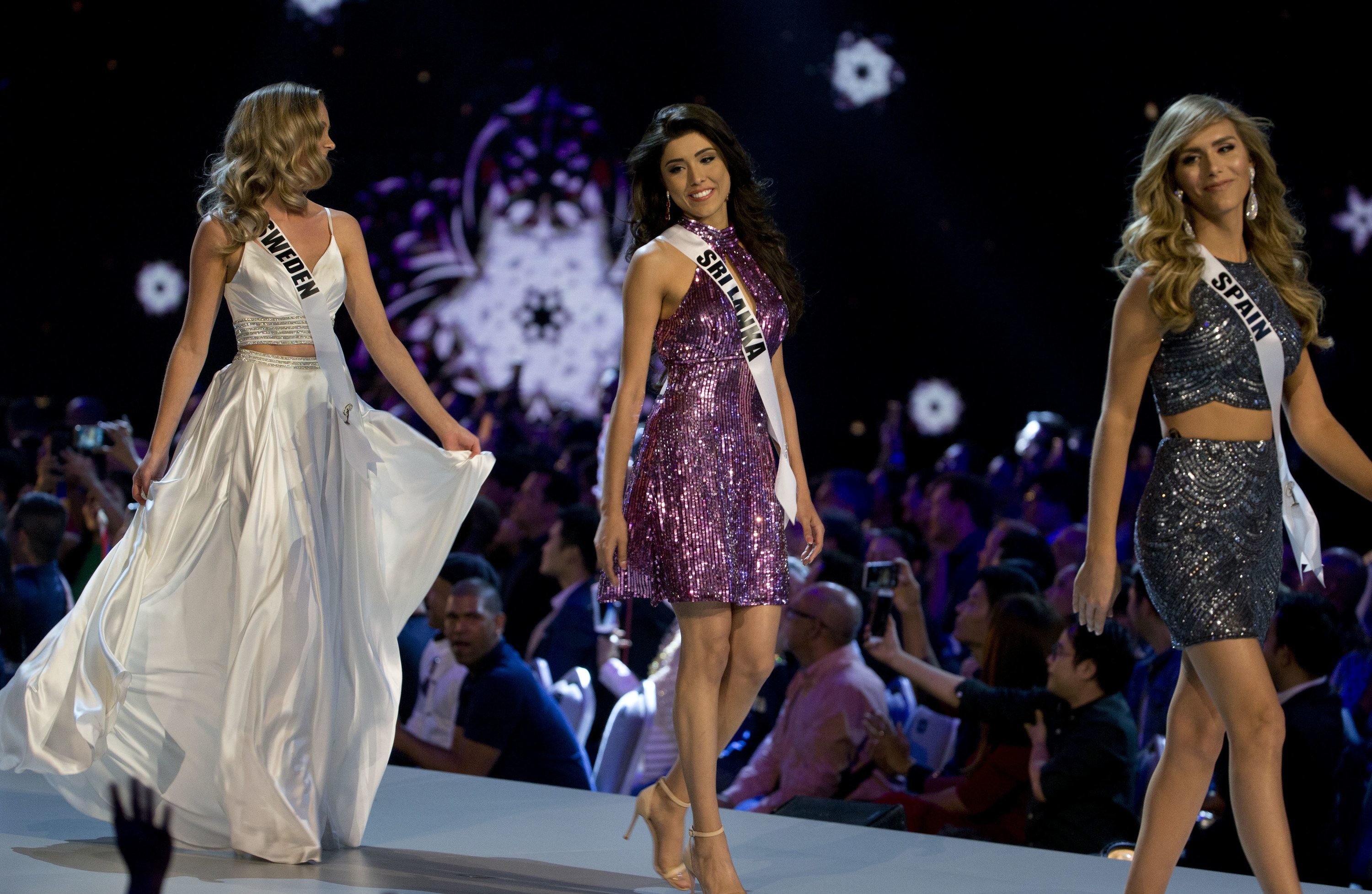 Three beauty pageant contestants on a runway