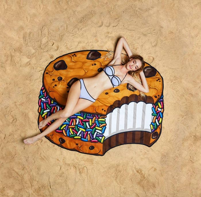A model lying on the large towel, which looks like a chocolate chip cookie ice cream sandwich with rainbow sprinkles and a bite taken out of it