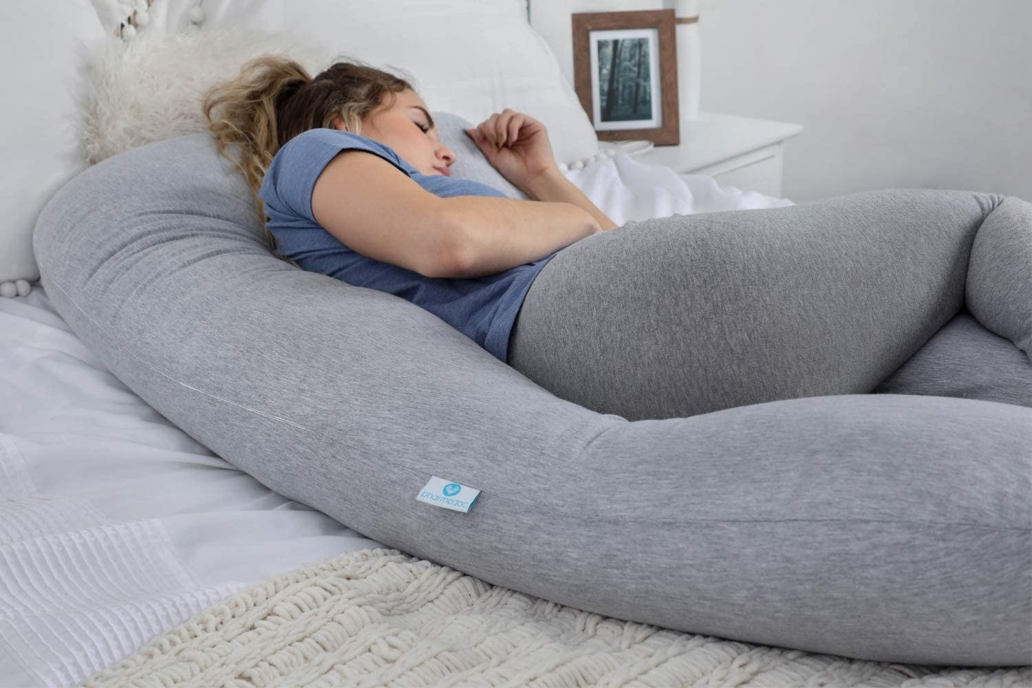 A person sleeping on their side with a long U-shaped pillow around them