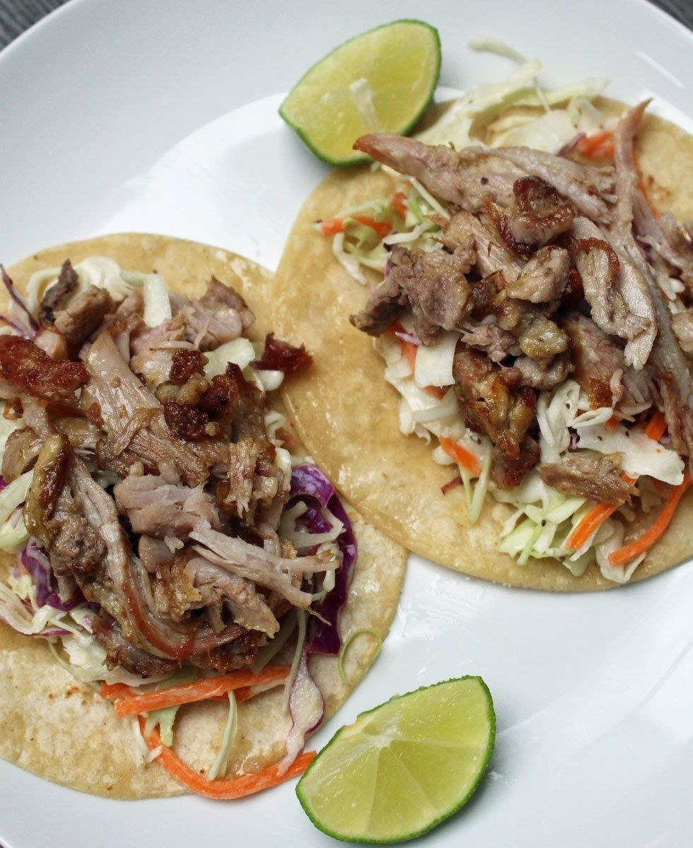 Two carnitas tacos with slaw on the bottom and a lime wedge on the side.