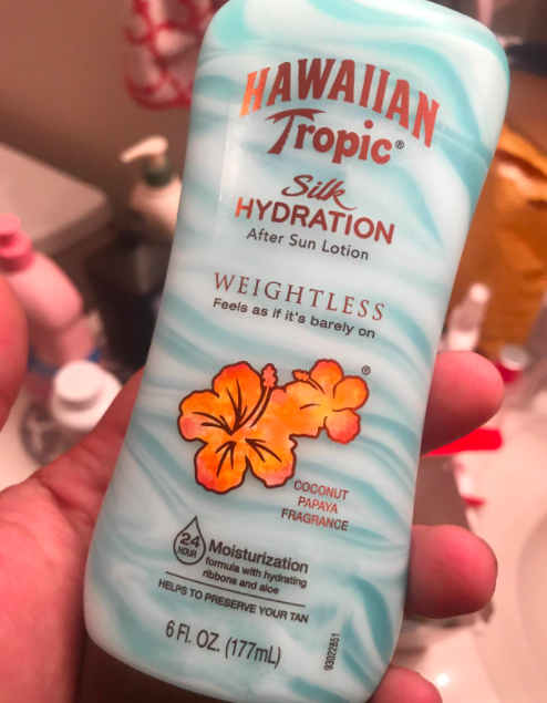 A reviewer holding a bottle of the Hawaiian Tropic after sun lotion