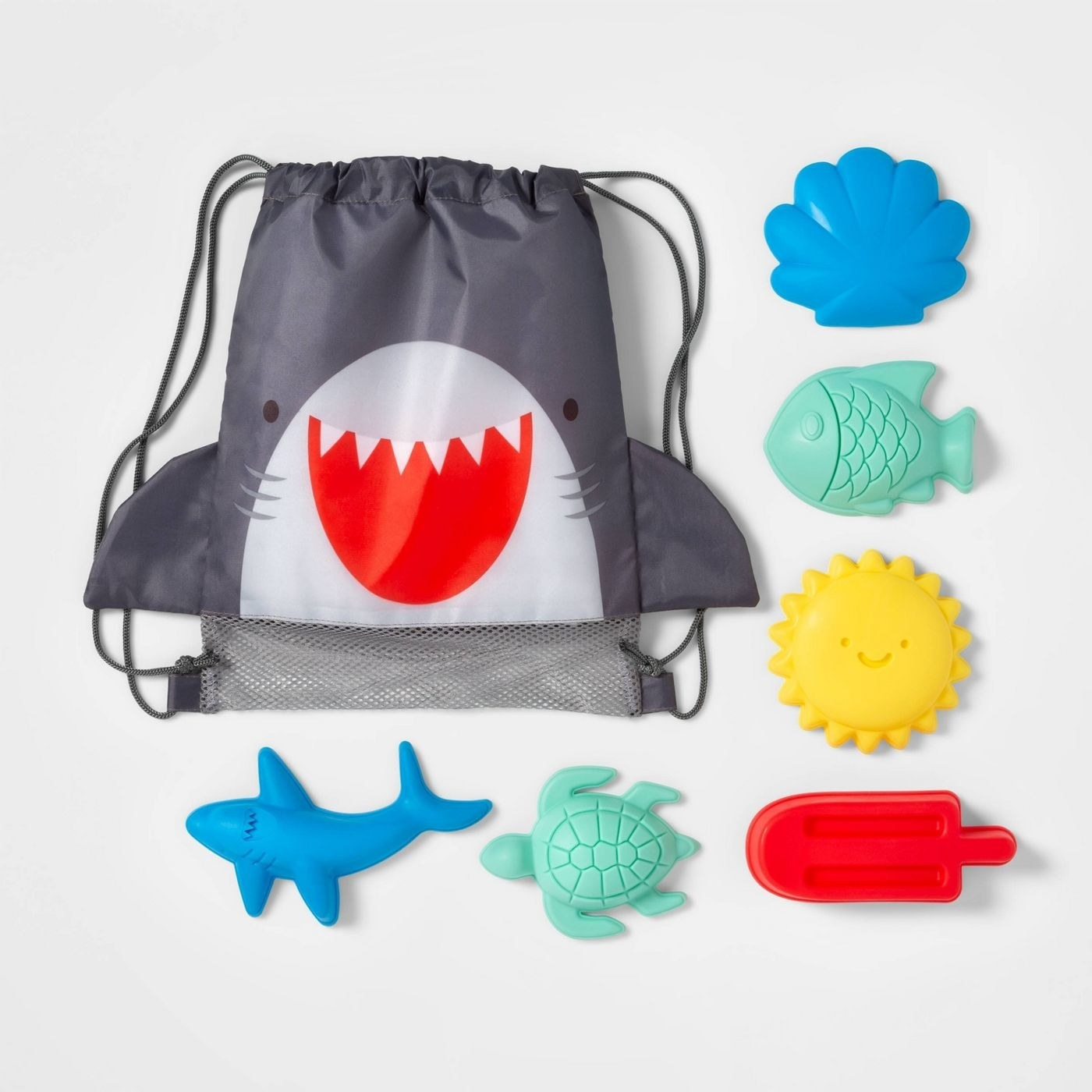 The mesh-bottomed shark face backpack complete with fins surrounded by six molds: a shark, turtle, popsicle, sun, fish, and shell